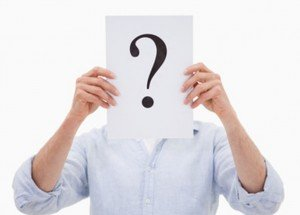 Portrait of a man hiding his face behind a question mark against a white background