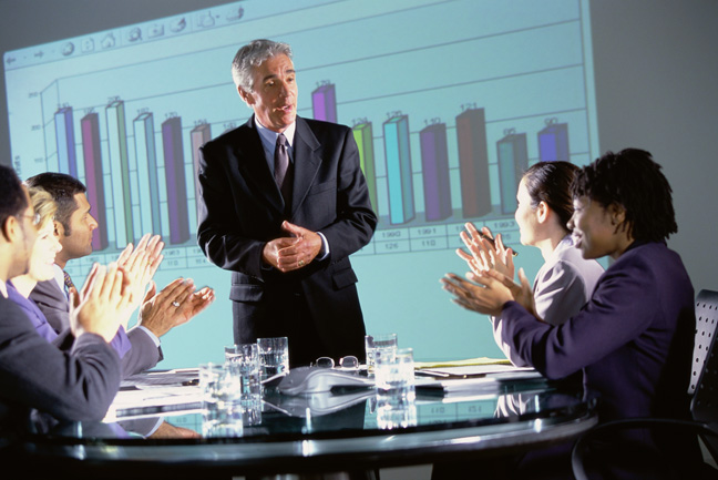 Business executives clapping at a presentation in