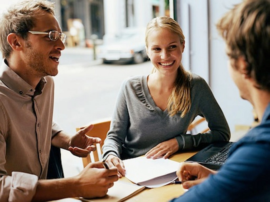 Young woman having business meeting in cafe with two men, smiling